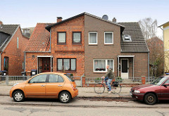 Doppelhaus mit unterschiedlich gestalteter Klinkerfassade; parkende Autos, Radfahrer - Lübeck Moisling.