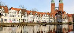 Wohnhäuser an der Untertrave in der Hansestadt Lübeck - Wäsche hangt zum Trocknen auf der Leine an der Trave - Türme vom Lübecker Dom.