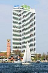 Segelboot auf der Trave - Maritim Hotel und alter Leuchtturm. Das Hotel wurde 1974 fertig gestellt und hat mit 36 Etagen eine Höhe von 119 m - der alte Leuchtturm wurde 1827 aus rotem Backstein 1827 in klassizistischem Stil errichtet und hat eine Höh