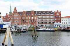 Historische Backsteingebäude und neues modernes Verwaltungsgebäude am Hafen an der Untertrave in der Hansestadt Lübeck - im Hintergrund der Kirchturm der St. Jacobikirche, eine der fünf evangelisch-lutherischen Hauptpfarrkirchen in der Lübecker Altst