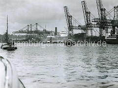 Kohlenfrachter am Kai des Kohlenschiffhafens  im Hamburger Hafen  - Verladekräne; im Hintergrund sind auf dem gegenüber liegenden Elbufer Gebäude in Altona zu erkennen.