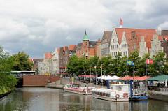 An der Obertrave in der Hansestadt Lübeck - Schiffsanleger mit Ausflugsbooten; Uferpromenade mit Sonnenschirmen und Aussengastronomie / Cafés und Restaurants.