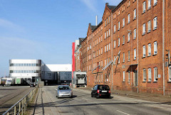Moderne Industriearchitektur, Verwaltungsgebäude und historischer Backsteinspeicher am Ufer der Trave / Hafenstrasse in der Hansestadt Lübeck.