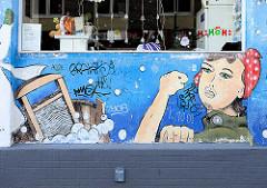 Grafitti an einer Hauswand in Hamburg St. Pauli - Wäscherin mit Kopftuch und Waschbrett / Zuber, Seifenschaum zeigt die Geste fuck you.
