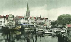 Historische Ansicht vom Altstadthafen und Gebäuden an der Trave in der Hansestadt Lübeck - Nachbau einer Kogge mit Kanonen, Barkassen; Kirchturm der Lübecker Petrikirche.
