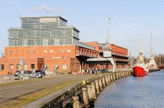 Hafenareal auf der Wallhalbinsel in Lübeck - ehem. Verteidigungsanlage und Hafen; zum Büro umgebautes Lagerhaus - Küstenschiff mit rotem Rumpf an der Kaimauer, Hafenkräne.
