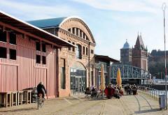 Altes Hafengebäude - historische Industriearchitektur an der Trave in der Hansestadt Lübeck - Café am Wasser; im Hintergrund der Ziegelturm der Hubbrücke und der massive Turm vom Burgtor.