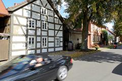 Fachwerkgebäude, fahrendes Auto / Cabrio - Strasse in Schlepzig / Spreewald.