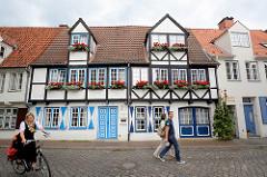Fachwerkarchitektur in der Hansestadt Lübeck - blau gefasste Türen und Fensterluken, Blumenkästen mit blühenden Blumen.