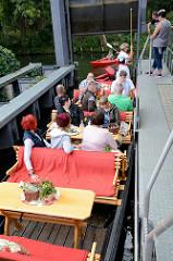 Ein Spreekahn mit Touristen an Bord in einer Schleuse in Schlepzig - das Boot passt gerade in die Schleusenkammer.