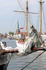 Masten und Bugsprit historischer Segelschiffe beim Anleger Priwall  - im Hintergrund der Kirchturm der St. Lorenzen Kirche von Travemünde.