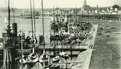 Historische Aufnahme vom Hafen in Travemünde - Segelboot und Dampfer am Steg; im Hintergrund die Strandpormenade und der Kirchturm der St. Lorenz Kirche.