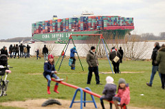 Kinderspielplatz in Grünendeich an der Elbe - Kinder auf der Schaukel und Wippe - im Hintergrund das auf einer Sandbank festgefahrene Containerschiff CSCL Indian Ocean.