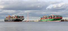 Der Continerfrachter Hanjin Asia fährt auf der Elbe bei Stade - daneben die festgefahrene, havarierte CSCL Indian Ocean.