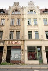 Wohnhäuser mit Jugendstildekor / Floralen Stuckelementen - Geschäfte im Erdgeschoss; eines der Gebäude ist renoviert, das andere benötigt Farbe; alt + neu.