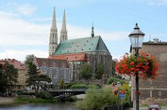 Blick vom Zgorzelec - Ufer der Lausitzer Neiße; Laternenmast mit blühenden Geranien - im Hintergrund die evangelische Pfarrkirche St. Peter und Paul und das Waidhaus.
