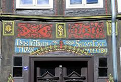 Mit Schnitzerei und lateinischer Inschrift versehener Türsturz eines historischen Fachwerkgebäudes in Goslar / Harz.