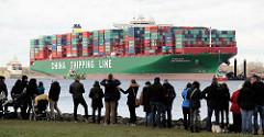 Schaulustige am Elbufer in Grünendeich blicken zum havarierten Containerfrachter CSCL Indian Ocean.