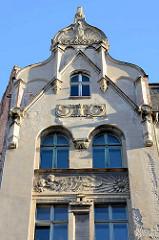 Fassadendetail eines Jugendstilgebäudes in Görlitz - Putten, Engelsköpfe pusten Wind zur Sonne / Blüte; im Giebel ein Adler über Schlangennest.