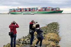 Fotografen am Elbufer bei Grünendeich auf einer Steinbuhne - auf der Elbe, der auf einer Sandbank festgefahrene Containerfrachter CSCL Indian Ocean.
