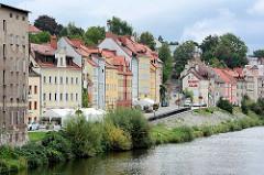 Wohnhäuser und Uferpromenade an der Neiße in Zgorzelec; polnischer Grenzpfahl am Ufer.