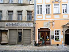 Wohn- und Geschäftshäuser in Görlitz - Geschäfte im Erdgeschoss; eines der Gebäude ist renoviert, das andere benötigt Farbe; alt + neu.