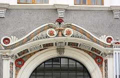 Farbig gestaltetes Eingangsdekor - Stuckdekoration am Türsturz eines historischen Gebäudes in Görlitz.