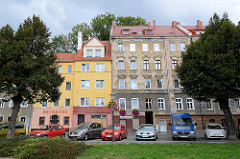 Wohnhäuser und Parkplätze an der Uferpromenade der Lausitzer Neiße in Zgorzelec - eines der Gebäude ist restauriert und mit Fassadenfarbe versehen, das andere Gründerzeitgebäude hat abbröckelnden Putz und ist renovierungsbedürftig.