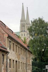 Renovierungsbedürftiges, verfallenes einstöckiges Mietshaus - Doppeltürme der St. Peter und Paulkirche in Görlitz.