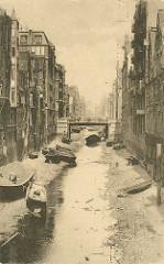 Historisches Bild vom Herrengrabenfleet in der Hamburger Neustadt - es ist Ebbe und die Schuten und Barkassen sind trockengefallen, sie liegen im Schlick. Hohe Speichergebäude beiderseits vom Fleet.