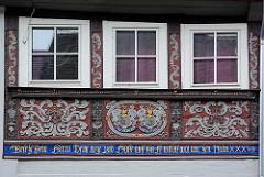 Schnitzerei im Fachwerk eines historischen Gebäudes in der Stadt Goslar - biblischer Sinnspruch im Fachwerkbalken - Namen der Eheleute mit Blumendarstellung  - Rankornamentik / Arabesken.