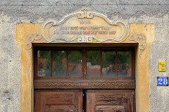 Jugenstilschmuck über Oberlicht einer Eingangstür - Inschrift 1910, Kehr erst vor deiner Tür - als dann komm und hilf auch mir.