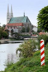Blick vom Ufer der Neisse in Zgorzelec zur evangelischen Pfarrkirche St. Peter und Paul und das Waidhaus - im Vordergrund der Grenzpfahl in den polnischen Farben rot / weiss.