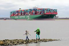 Kinder spielen auf einer Steinbuhne am Elbufer - auf der Elbe der havarierte, aufgelaufene Containerfrachter CSCL Indian Ocean.