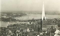 Historische Luftaufnahme der Hamburger Altstadt - Dächer der Innenstadt bei der Mönckebergstrasse - Kirchturm u. Kirchenschiff der St. Petrikirche. Im Hintergrund die Binnenalster mit der Lombardsbrücke und die Aussenalster mit Segelbooten.