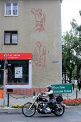 Schlichtes Wohnhaus mit Rauhputzfassade und Fresko / Fassadendekor, arbeitende Männer  - Arbeiter Zimmermann und Maurer.