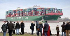 Schaulustige am Ufer der Elbe  in Grünendeich blicken zum havarierten Containerfrachter CSCL Indian Ocean.