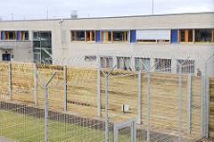 Gefängniszaun mit Stacheldraht - Sichtschutz aus Holzbrettern, Gefängnisblock in der Hamburger JVA Billwerder.
