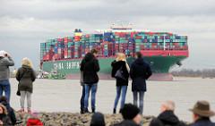 Schaulustige am Elbufer in Grünendeich blicken zum auf Grund gelaufenen  Containerschiff CSCL Indian Ocean.