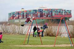 Kinderspielplatz in Grünendeich an der Elbe - Kinder auf der Schaukel; im Hintergrund das havarierte Containerschiff CSCL Indian Ocean.