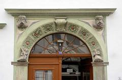 Eingangsdekor in Görlitz - Blumenfliesen im Halbrund über dem Türsturz - weibliche Figuren, Männerköpfe.