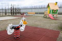 Kinderspielplatz mit Schaukeltier, Holzhaus mit Rutsche / Frauengefängnis Hamburg Billwerder.