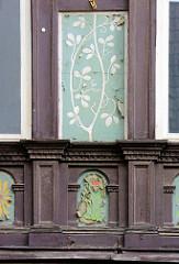 Historisches Geschäftshaus in der Langen STrasse von Blankenburg / Harz - Malerei in der Gebälkfüllung; die Farbe blättert ab.