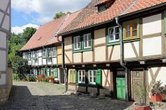 Historische Handwerkerhäuser, niedrige Türen - Fensterlucken; Blumen vor der Haustür - Grauer Hof in Halberstadt / Baudenkmale der Stadt.