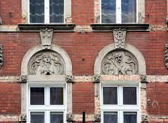 Fassadenschmuck  eines Wohnhauses in der  Altstadt von Świdnica / Schweidnitz; Jugendstildekor - betende Frau mit Kreuz - bärtiger Bergarbeiter / Schmied mit Hammer.