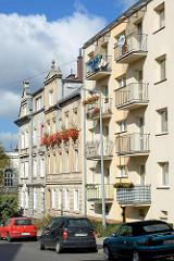 Architektur in Bunzlau / Bolesławiec - schlichte Hausfassade eines Mietshauses mit Balkons - mehrstöckige Wohnhäuser mit Geranien vor den Fenstern - Gründerzeitgebäude.