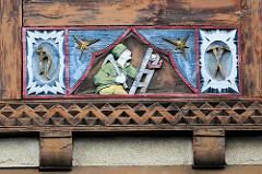 Fachwerkschnitzerei  - Bergmann /  bei der Arbeit - auf einer Leiter mit Hacke und offenem Grubenlicht - offene Froschlampe; Fassadendekoration in Goslar / Harz.