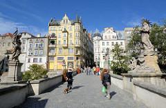 Skulpturen / Brückenfiguren der Johannisbrücke / Brücktorbrücke - mittelalterliche Steinbogenbrücke in Kłodzko / Glatz; Blick zur Altstadt - Touristen überqueren die historische Brücke