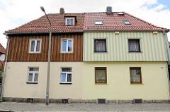 Siedlungshäuser mit Holz verkleidete Fassade; unterschiedlich farblich abgesetzte Fassadengestaltung - Architekturbilder aus  Wernigerode.