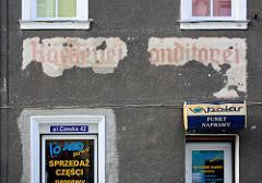 Moderne polnische Werbeschilder an Fenster und Hausfassade - alte freigelegte Inschrift Bäckerei Konditorei in Glatz / Kłodzko .
